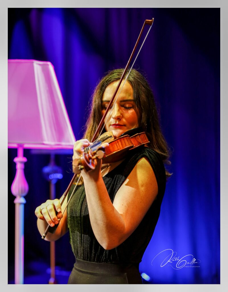 Maria Ryan playing the fiddle under the lights of Glór.