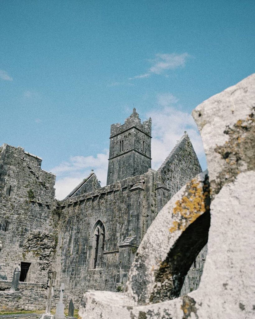 The ruins of Quin Abbey sits below the blue sky.